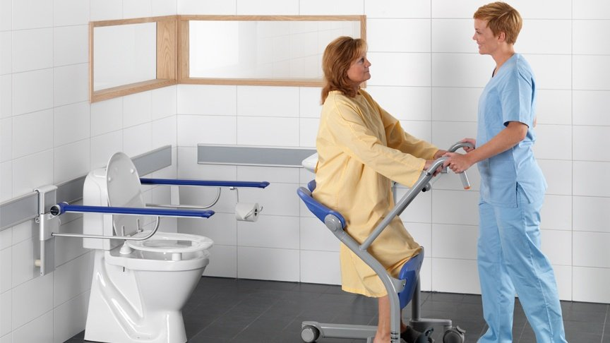 ArjoHuntleigh-Products-Patient-Transfer-Solutions-Standing-and-Raising-Aids-Sara-Stedy-Female-Patient-and-Carer-transfer-to-toilet-1